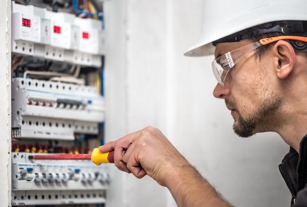 Mann, ein elektrotechniker, der in einer schalttafel mit sicherungen arbeitet. installation und anschluss von elektrischen geräten. nahansicht.