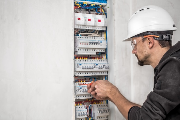 Mann, ein elektrotechniker, der in einer schalttafel mit sicherungen arbeitet. installation und anschluss von elektrischen geräten.