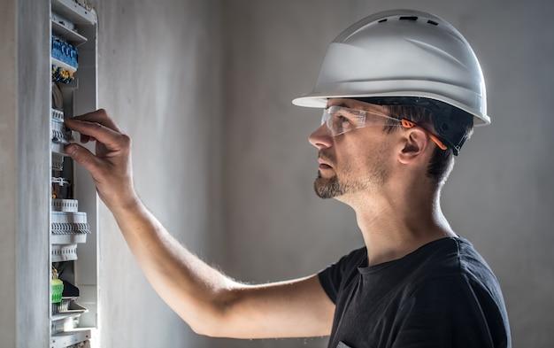 Mann, ein elektrotechniker, der in einer schalttafel mit sicherungen arbeitet.