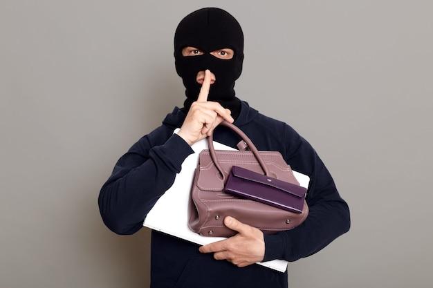 Mann einbrecher hält laptop