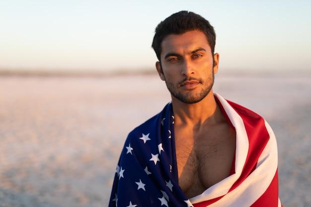 Mann eingewickelt in der amerikanischen flagge, die auf dem strand steht