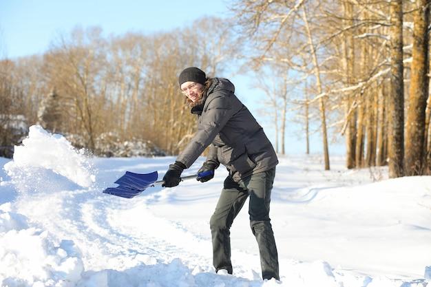Mann entfernt schnee mit schaufel von der straße im wintertag
