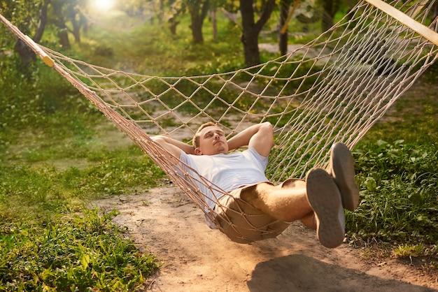 Mann entspannen im hängemattengarten. sommerstimmung im grünen wald