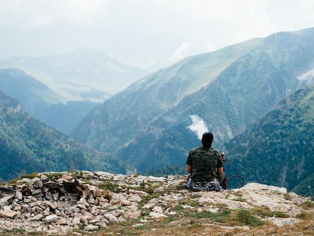 Mann entspannen in den bergen auf naturlandschaft frische landschaft neuluftnebelsonnenlicht.