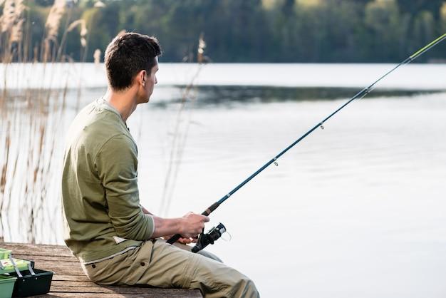 Mann entspannendes angeln oder angeln am see