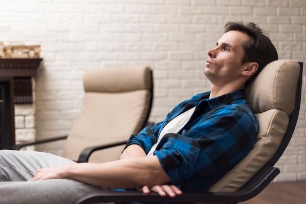 Mann entspannt auf einem schaukelstuhl