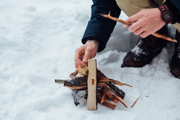 Mann entzündet lagerfeuer im schneebedeckten winterwetter