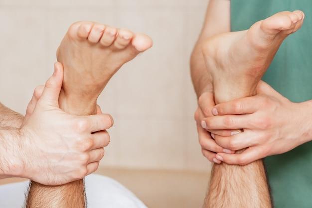 Mann erhält beinmassage an seinen füßen von zwei massagetherapeuten, nahaufnahme.