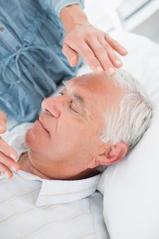 Mann erhält reiki-behandlung von therapeuten
