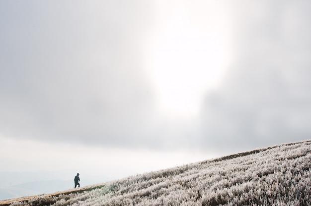 Mann erhebt sich am berg gefrorenen hügel.