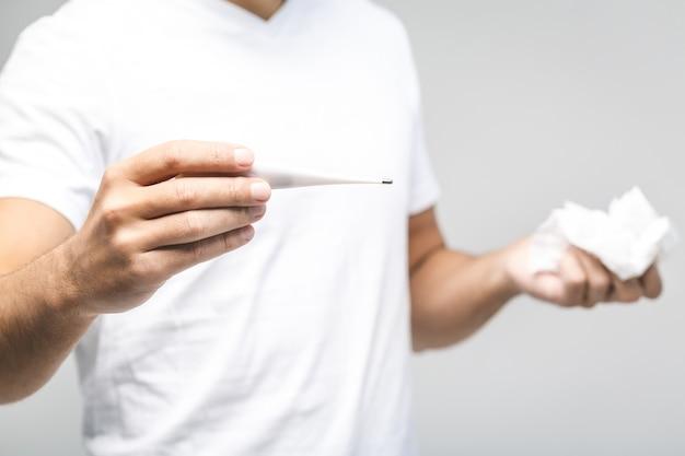 Mann erkältet, grippe, laufende nase. gesundheitswesen und medizinisches konzept isoliert auf weiß. temperatur prüfen. nahansicht.