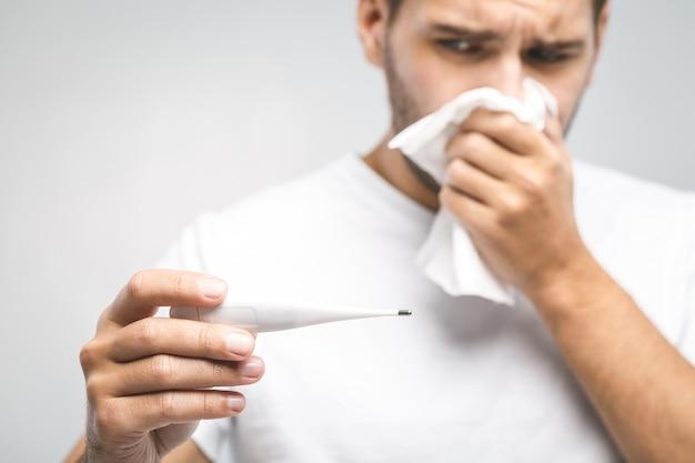 Mann erkältet, grippe, laufende nase. gesundheitswesen und medizinisches konzept isoliert auf weiß. temperatur prüfen.