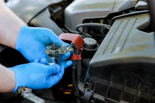 Mann ersatzbatterie auto mit mechaniker, der im autoreparaturdienst arbeitet.