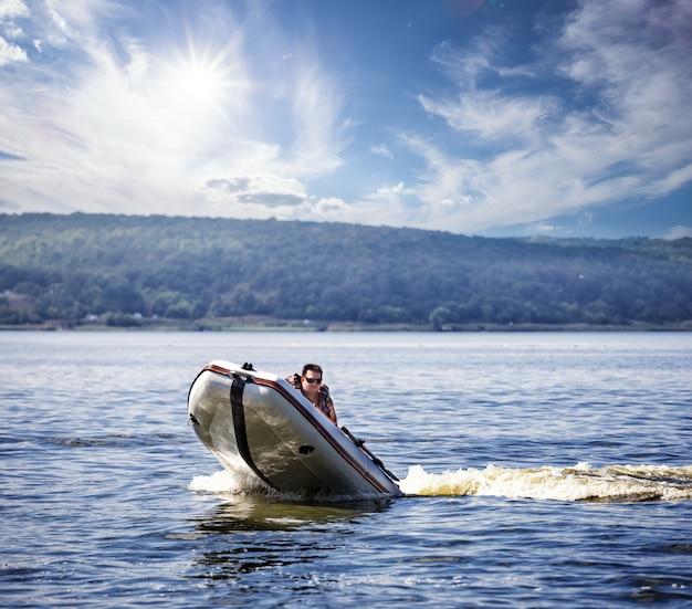 Mann fährt ein weißes motorboot