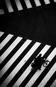 Mann fährt fahrrad auf einem zebrastreifen in japan