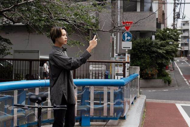 Mann fährt fahrrad in der stadt und macht selfie mit smartphone