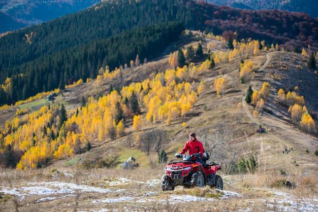 Mann fährt geländewagen auf einer bergstraße, die auf die bergspitze führt