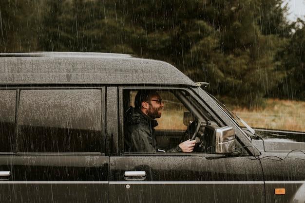 Mann fährt unter dem regen