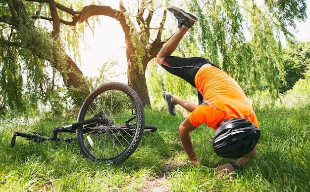 Mann fällt vom fahrrad auf dem weg auf dem land