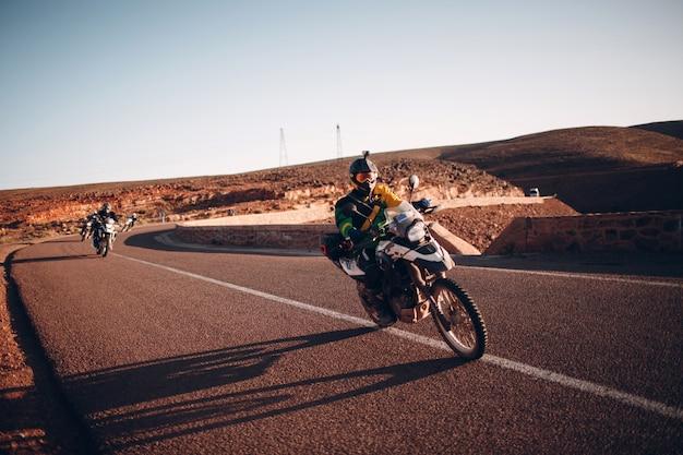 Mann fahrer reitet mountain adventure bike auf straße in der wüste. motocross in sahara, marokko.