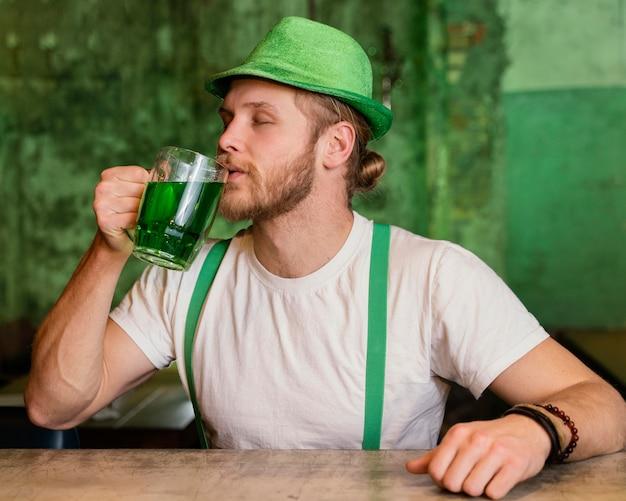 Mann feiert st. patricks tag mit getränk