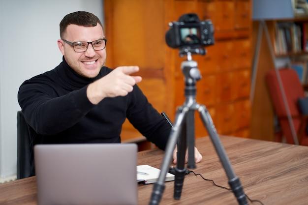 Mann filmt videoblog vor der kamera mit stativ für online-follower. in social media, influencer, neuer technologie und internetkonzept