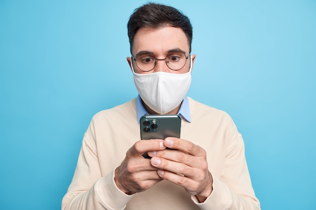 Mann fokussiert überrascht auf handy-display trägt runde brille überprüft newsfeed per smartphone lässig gekleidet dressed Kostenlose Fotos