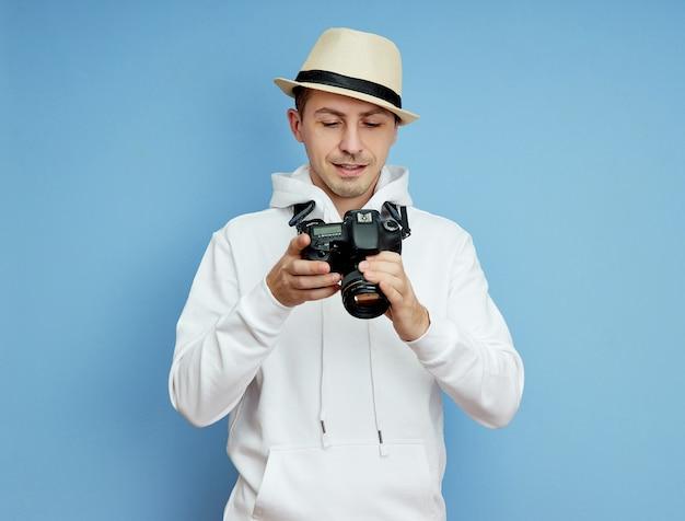 Mann fotograf mit einer spiegelreflexkamera in den händen macht fotos