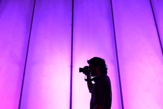 Mann fotografierte das halten einer kamera auf buntem hintergrund