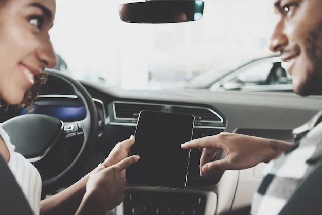 Mann-frau, die auto-computer-system-tablet kontrolliert.