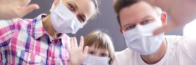 Mann, frau und kleines mädchen in den schützenden medizinischen masken auf dem gesicht, das vor der laptop-kamera winkt