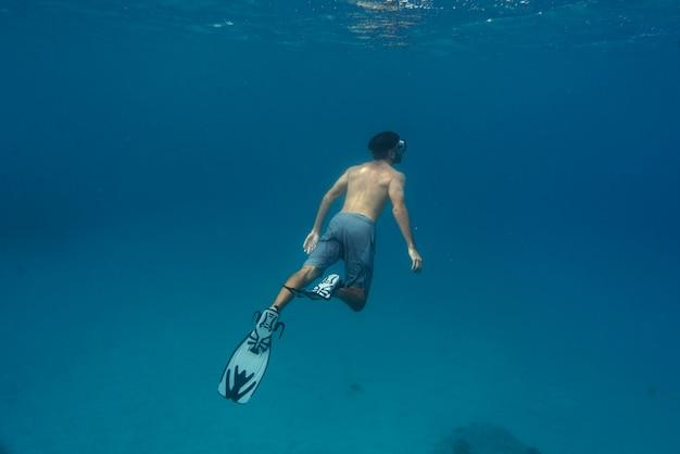 Mann freitauchen mit flossen unter wasser
