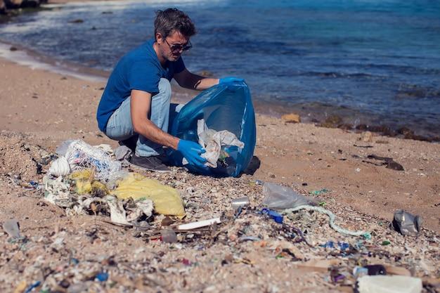 Mann freiwillig in blauem t-shirt mit großer tasche zum sammeln von müll am strand. umweltverschmutzungskonzept