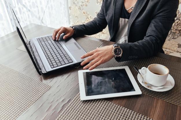 Mann freizeitkleidung in einem café kaffee trinken und einen laptop verwenden