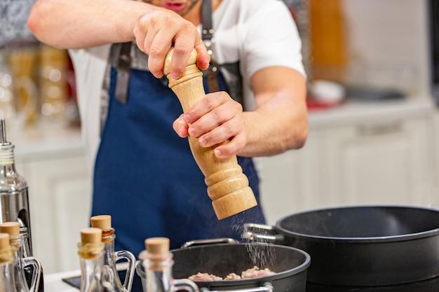 Mann fügt gemahlenen pfeffer von der mühle in bratpfanne auf ofen hinzu. anschauen konzept