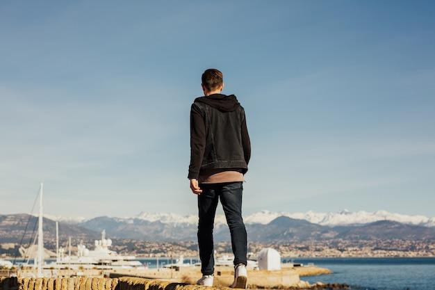 Mann gehen am wasser und genießen sie den blick auf das meer.
