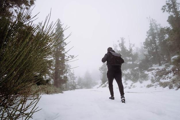 Mann geht auf schnee in berglandschaft
