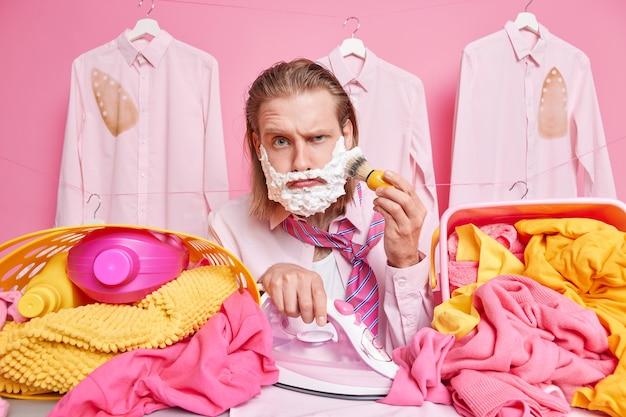 Mann geht morgens mit kleidung zur arbeit, geht zu einem geschäftstreffen, ist in eile rasiert und bügelt kleidung gleichzeitig posiert in der nähe großer wäschehaufen