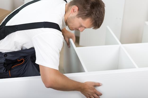 Mann gekleidet in den gesamtmontagemöbeln der arbeiter, die auf dem boden in neuem zuhause sitzen. diy, heim- und umzugskonzept