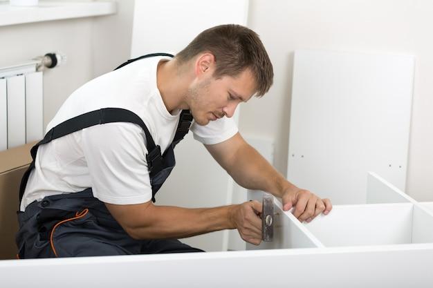 Mann gekleidet in den gesamtmontagemöbeln der arbeiter im neuen zuhause. diy, heim- und umzugskonzept