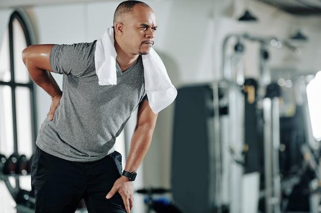 Mann gemischter abstammung, der nach dem training im fitnessstudio unter kreuzschmerzen leidet
