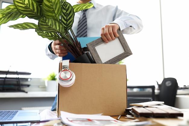 Mann geschäftskleidung legt dinge in kiste im büro. manipulative methoden, die menschen zur entlassung beeinflussen. guy stellt einen blumentopf und persönliche gegenstände in die schachtel. umzug der mitarbeiter in ein neues büro