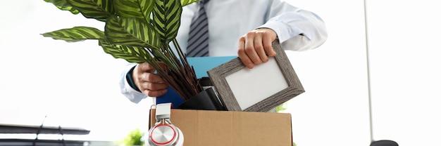 Mann geschäftskleidung legt dinge in kiste im büro