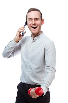 Mann geschäftsmann, lehrer am telefon sprechen und sport treiben hält in der hand eine rote hantel. emotionales porträt. isoliert auf weißem hintergrund