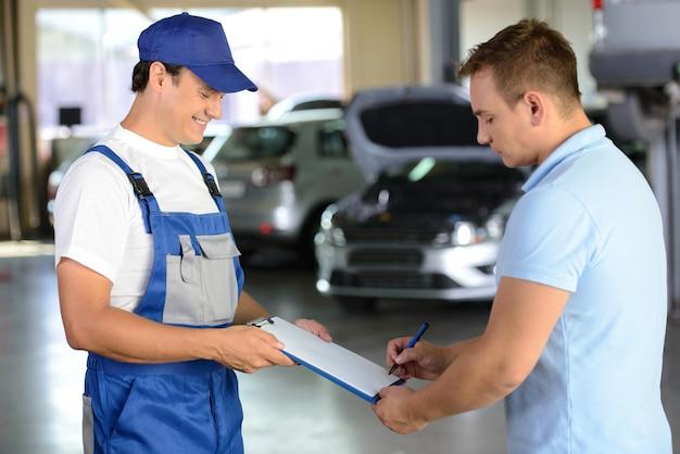 Mann gibt dem kunden ein notizbuch mit aufzeichnungen der geleisteten arbeit.
