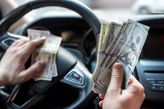 Mann gibt dollars, während er im auto sitzt. konzept des einkaufens, geld