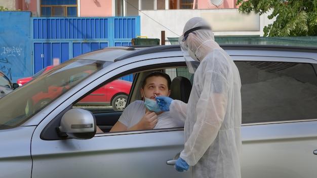 Mann gibt einen test auf coronavirus in seinem auto durch das fenster.
