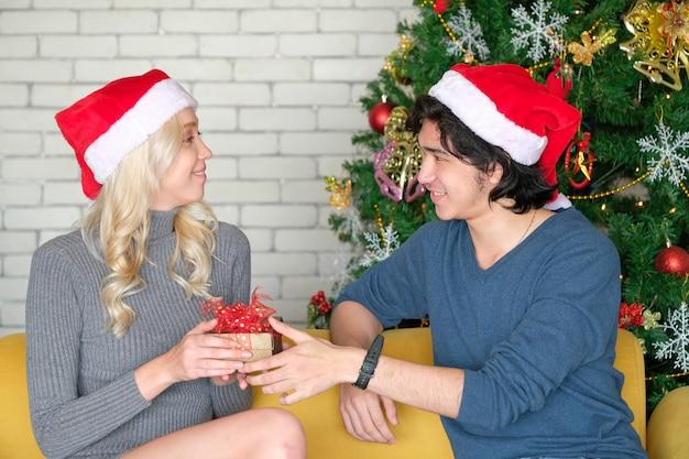 Mann gibt einer frau am weihnachtstag eine geschenkbox