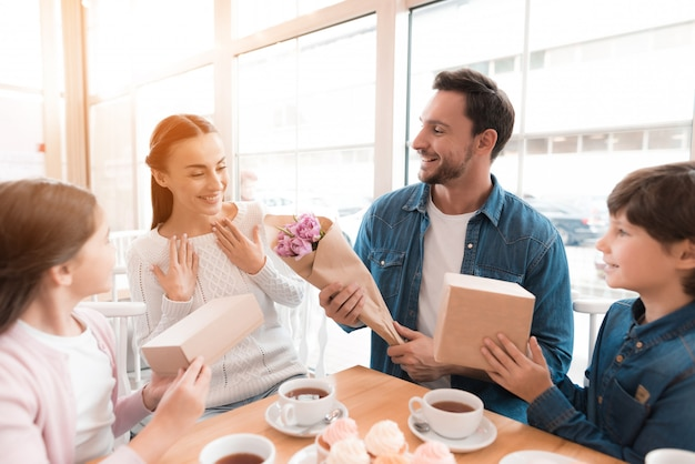 Mann gibt überraschten frauen-familien-café blumen.