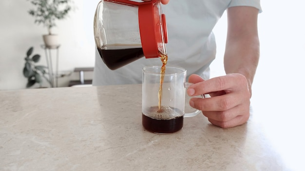 Mann gießt einen frisch gebrühten kaffee in eine glasschale vom glasserver. pourover, v60.